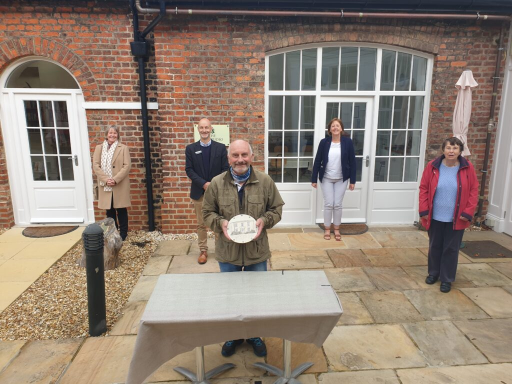 Les Simpson with the plaque he created with fellow residents and Middleton Hall directors